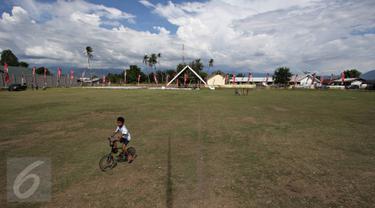 Seorang anak bermain sepeda di Lapangan Sepak Bola Kota Palu, Sigi, Sulteng, Selasa (8/3). Rencananya di lapangan tersebut, Wapres Jusuf Kalla dan istrinya, Mufida Kalla akan menyaksikan fenomena Gerhana Matahari Total. (Liputan6.com/Immanuel Antonius)