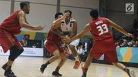 Tiga pebasket putra Indonesia mencoba menahan pemain India saat turnamen invitasi sekaligus tes event jelang Asian Games 2018 di Jakarta, Jumat (9/2). Indonesia kalah 66-55. (Liputan6.com/Helmi Fithriansyah)