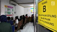 Wajib pajak dibantu petugas mengisi data di ruang Kelas Pajak EFILING di Kantor Pelayanan Pajak Pratama Jakarta, Kamis (29/3). Lonjakan wajib pajak terjadi jelang batas akhir penyampaian laporan SPT PPh orang pribadi. (Merdeka.com/Iqbal Nugroho)