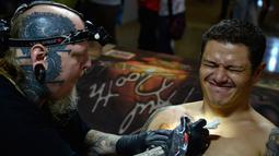 Pengunjung terlihat kesakitan saat ditato oleh seniman Paul Booth di edisi 5 Konvensi Internasional Paradise Tatto, di San Antonio de Belen, San Jose, (8/5). Lebih dari 300 seniman tato berpartisipasi di acara ini.(AFP PHOTO/Ezequiel Becerra)