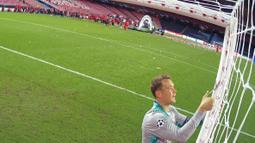 Kiper Bayern Munchen, Manuel Neuer, menggunting jaring gawang usai menjuarai Liga Champions di Stadion The Luz, Portugal, Senin (24/8/2020). Bayern Munchen berhasil menjadi juara usai menaklukkan PSG 1-0. (Lluis Gene/Pool via AFP)
