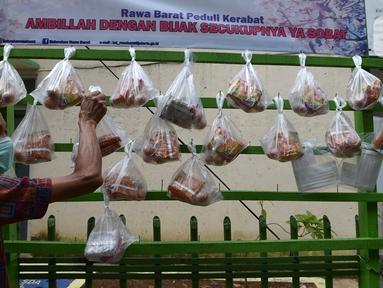 Warga mengambil sembako yang digantung di rak kayu sisi jalan di kawasan Rawa Barat, Jakarta Selatan, Kamis (14/5/2020). Selama masa pandemi COVID-19, pihak kelurahan dan masjid sekitar menyediakan paket berisi mi instan, telur, dan masker untuk warga yang membutuhan. (merdeka.com/Imam Buhori)