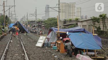 Pengungsi banjir mendirikan tenda di jalur rel kereta commuterline Tangerang-Duri di Kembangan Baru, Jakarta, Jumat (3/1/2020). Jalur rel yang nonaktif sementara karena banjir dimanfaatkan warga sekitar untuk mendirikan tenda darurat karena rumah mereka masih terendam. (Liputan6.com/Faizal Fanani)