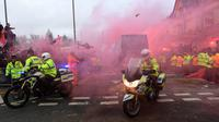 Bus pemain Manchester City dikawal ketat oleh polisi saat melintasi pendukung Liverpool jelang pertandingan Liga Champions di stadion Anfield di Liverpool (4/4). (AFP Photo/Paul Ellis)