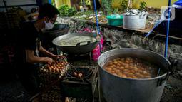 Petugas Taruna Siaga Bencana (Tagana) merebus telur di Dapur Umum Kementerian Sosial di GOR Otista, Jakarta, Minggu (21/2/2021). Dalam sehari, petugas menyiapkan hingga 6.000 paket nasi kotak yang didistribusikan ke 11 kelurahan terdampak banjir. (Liputan6.com/Faizal Fanani)
