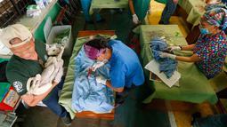 Para dokter hewan lakukan kebiri pada hewan-hewan di Payatas, Manila, Filipina, Selasa (26/9). Kasus rabies di Filipina termasuk yang tertinggi di dunia. HIS perkirakan 200 orang meninggal tiap tahunnya melalui gigitan anjing. (AP Photo/Bullit Marquez)