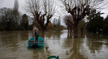 Marcel Leclercq menggunakan perahu di jalan yang banjir di pulau Vaux, sebelah barat Paris, (30/1). Sungai Seine yang meluap akibat hujan deras dalam 50 tahun telah menelan dermaga di Paris, Prancis. (AP Photo / Thibault Camus)