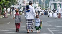 Seorang pria bersama dua orang anak berjalan menuju tempat pelaksanaan salat Idul Fitri 1438 H di kawasan Jatinegara, Jakarta, Minggu (25/7). Ruas Jalan Jatinegara Barat disulap menjadi tempat pelaksanaan salat Ied. (Liputan6.com/Yoppy Renato)
