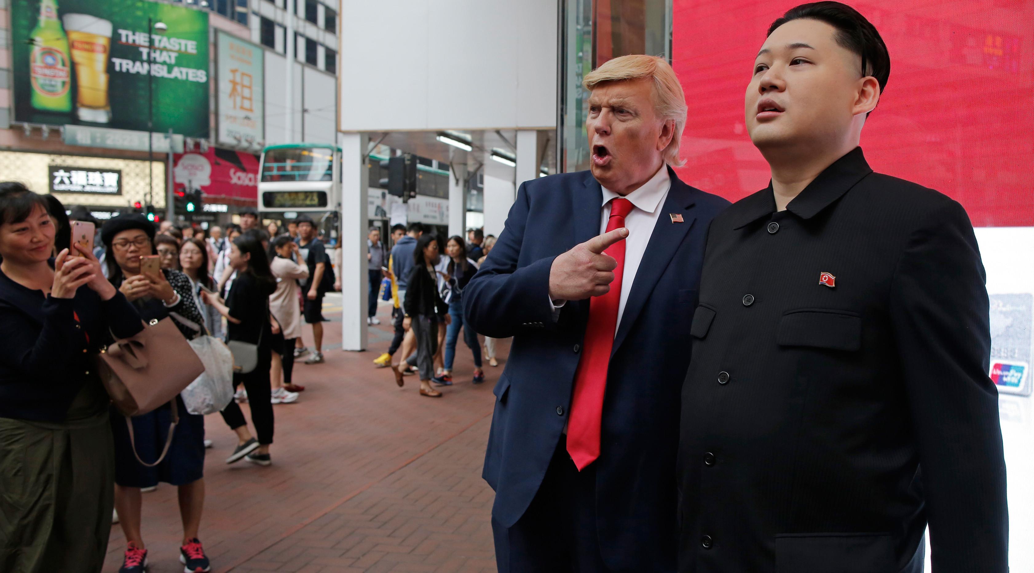 Pengunjung mengambil gambar Reggie Brown yang berdandan mirip Pemimpin Korea Utara, Kim Jong-un dan Dennis Alan yang berdandan mirip Presiden AS Donald Trump saat mempromosikan Rugby Sevens di pusat kota Hong Kong, 7 April 2017. (AP Photo/Kin Cheung)