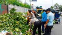 Personel Polsek Tampan Pekanbaru mengangkut tumpukan sampah di sebuah ruas jalan. (Liputan6.com/M Syukur)