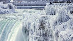 Pengunjung mengambil gambar Horseshoe Falls di Air Terjun Niagara yang membeku di Ontario, Kanada, Jumat (29/12). Cuaca dingin melanda sebagian besar wilayah utara Amerika Serikat di akhir tahun ini. (Aaron Lynett/Canadian Press via AP)
