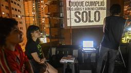 """Aktivis @lanuevabandadelaterraza memproyeksikan slogan bertuliskan """"Duque berubah dua tahun dan masih tidak bisa berjalan sendiri"""", mengacu pada Presiden Kolombia Ivan Duque, di dinding gedung, sebagai bagian dari cara baru untuk melakukan protes di Medellin, 9 Agustus 2020. (JOAQUIN SARMIENTO/AFP)"""