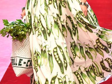 Model berjalan membawa tas besar mirip tas pasar dan mengisinya dengan sayuran untuk koleksi Dolce & Gabbana Spring/Summer 2018 di Milan Fashion Week, Minggu (24/9). (AFP PHOTO / Andreas SOLARO)