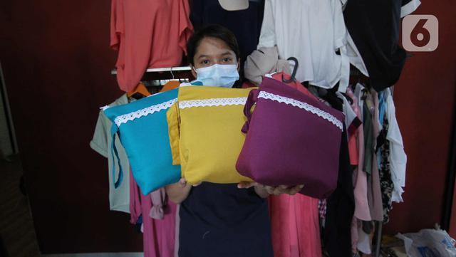 Pekerja menunjukkan hasil mukena yang telah selesai di Pinang, Kota Tangerang, Banten, Kamis (22/4/2021). Di bulan Ramadhan, produksi mukena di tempat tersebut meningkat 50 persen, dari 350 buah menjadi 700 buah per minggu dengan harga Rp250 ribu hingga Rp500 ribu. (Liputan6.com/Angga Yuniar)