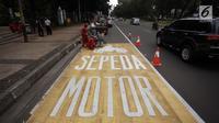 Pekerja menyelesaikan pengecatan rambu jalur kuning khusus sepeda motor di Jalan Medan Merdeka, Jakarta, Selasa (16/1).  Seperti diketahui, Mahkamah Agung (MA) membatalkan pergub larangan sepeda motor melintas di kawasan itu. (Liputan6.com/Arya Manggala)