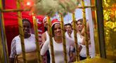 Narapidana perempuan tersenyum di balik jeruji penjara yang dihias dengan dekorasi Natal di Penjara Nelson Hungria, Rio de Janeiro, Kamis (13/12). Penjara ini mengadakan kompetisi menghias sel menggunakan dekorasi bernuansa natal. (AP/Silvia Izquierdo)
