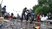 Seorang bapak berusaha menyalakan motornya yang mati akibat melewati banjir, Jakarta, Senin (6/2/2015).  Hujan yang turun sejak malam hingga kini membuat sejumlah ruas jalan tergenang air. (Liputan6.com/Faizal Fanani)