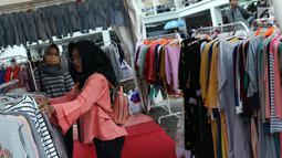 Pengunjung memilih koleksi pakaian di salah satu stand pada gelaran JakCloth di halaman Istora Senayan, Jakarta, Senin (4/6). JakCloth berlangsung hingga 10 Juni 2018. (Liputan6.com/Helmi Fithriansyah)