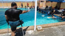 Majdi al-al-Tatar (kiri), instruktur renang saat melatih pemuda Palestina yang diamputasi di sebuah kolam renang di Kota Gaza (30/7/2019). Tatar melatih warga Palestina yang diamputasi untuk membantu mereka mempertahankan aktivitas fisik. (AFP Photo/Mahmud Hams)