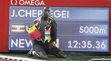 Pelari Uganda Joshua Cheptegei berpose dekat depan papan waktu usai memenangkan 5.000 meter putra pada final kejuaraan Monaco Diamond League 2020 di Stadion Louis II, Monako, Jumat (14/8/2020). Joshua memecahkan rekor dunia lari 5.000 meter dengan catatan waktu 12:35,36. (Eric Gaillard/Pool Via AP)