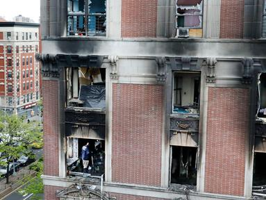 Petugas pemadam kebakaran memeriksa apartemen yang terbakar di kawasan Harlem, New York, Amerika Serikat, Rabu (8/5/2019). Kebakaran tersebut menewaskan enam orang termasuk di antaranya empat anak-anak. (AP Photo/Richard Drew)