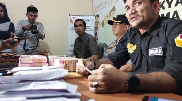 Ketua Bawaslu Pekanbaru Indra Kholid dengan uang diduga untuk serangan fajar di meja hasil tangkapan anggotanya.