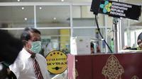 Pemeriksaan panas tubuh penumpang di kedatangan internasional Bandara Sultan Syarif Kasim II Pekanbaru. (Liputan6.com/M Syukur)