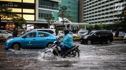 Sejumlah kendaraan melintas menerjang genangan air di kawasan Bunderan HI, Jakarta, Kamis (22/11). Genangan air hujan setinggi 40 cm tersebut disebabkan hujan deras yang melanda Jakarta pada siang hari. (Liputan6.com/Faizal Fanani)