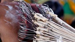Seorang umat Hindu mengaitkan rantai ke punggungnya saat Festival Thaipusam di Batu Caves, Kuala Lumpur, Malaysia (31/1). Di hari ini, para umat Hindu mencari berkah, memenuhi sumpah, dan berterima kasih. (AP Photo/Sadiq Asyraf)
