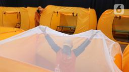 Petugas merapihkan tenda yang akan dijadikan tempat isolasi Covid-19 di gedung kesenian Tanah Abang, Jakarta, Minggu (17/5/2020). Gedung ini dijadikan tempat isolasi bagi masyarakat yang  akan mengikuti rapid test esok dilokasi tersebut. (Liputan6.com/Angga Yuniar)