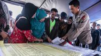 Anggota keluarga melihat daftar nama korban tenggelamnya KM Sinar Bangun di pelabuhan feri Danau Toba, Sumatera Utara, Rabu (20/6). Basarnas menerjunkan 70 personel untuk melakukan pencariankorban tenggelamnya KM Sinar Bangun. (AFP PHOTO/IVAN DAMANIK)
