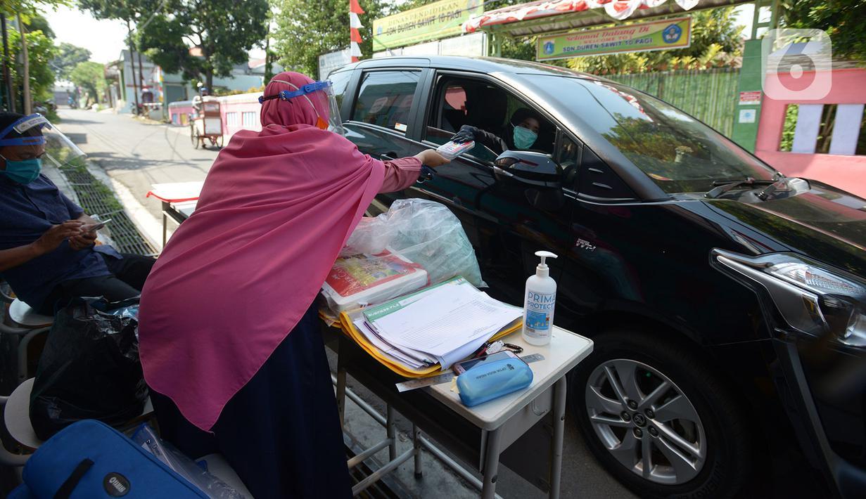 Guru SDIT Ibnu Sina memberikan tugas sekolah secara drive-thru kepada wali murid di Jakarta, Rabu (26/8/2020). Selama pembelajaran jarak jauh, siswa diwajibkan mengambil dan mengembalikan tugas di sekolah. (merdeka.com/Imam Buhori)