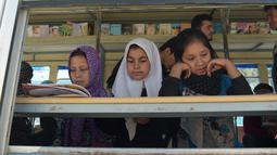 Anak-anak Afghanistan membaca buku dalam bus yang dijadikan perpustakaan keliling di Kabul, 4 April 2018. Perpustakaan keliling adalah inisiatif lulusan Oxford University, Inggris, Freshta Karim yang juga seorang pengungsi Afghanistan. (AFP/Shah MARAI)