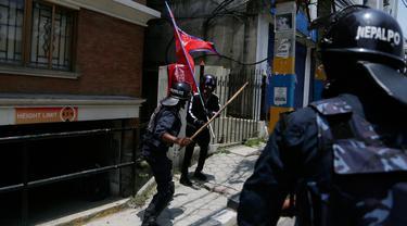 Seorang polisi Nepal memungkul pakai tongkat seorang pemuda saat protes di dekat kediaman perdana menteri menuntut penanganan yang lebih baik terhadap pandemi COVID-19 di Kathmandu, Nepal (11/6/2020).  (AP Photo/Niranjan Shrestha)