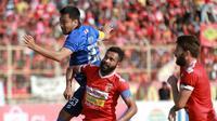 Kapten tim Arema, Hamka Hamzah, berduel dengan kapten Badak Lampung, Artur Bonai, di Stadion Sumpah Pemuda, Lampung (1/11/2019). (Bola.com/Iwan Setiawan)