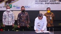Ketua Gapki Riau Jatmiko K Santosa mendampingi Gubernur Riau Syamsuar menandatangani MoU pembangunan rumah bagi buruh sawit. (Liputan6.com/M Syukur)