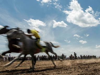Peserta memacu kudanya saat mendekati garis finish selama festival kuda Arab di Karhuk, Hassakeh, Suriah (5/5/2019). Festival kuda Arab tahunan ini sudah berlangsung keenam kalinya di daerah Al-Jwadea. (AP Photo/Baderkhan Ahmad)