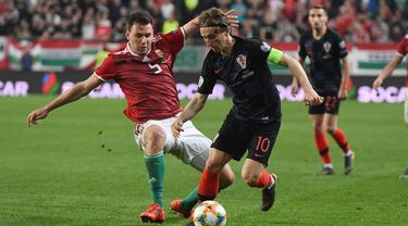 Aksi Luka Modrid melewati pemain Hungaria, Adam Szalai pada laga kedua babak kualifikasi Piala Eropa 2020 Grup E yang berlangsung di Stadion Groupama Arena, Budapest, Senin (25/3). Kroasia kalah 1-2 kontra Hungaria. (AFP/Attila Kisbenedek)
