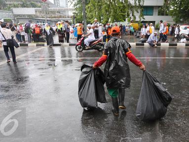 Seorang petugas kebersihan DKI Jakarta membawa sampah usai aksi damai 2 Desember di kawasan Jalan MH Thamrin, Jakarta, Jumat (2/12). Aksi damai 2 Desember digelar sebagai lanjutan dari aksi 4 November 2016. (Liputan6.com/Ferbian Pradolo)
