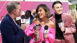 Penyanyi Agnez Mo (tengah) memegang piala iHeartRadio Music Awards 2019 di Los Angeles, California, AS, Kamis (14/3). Agnez Mo mengalahkan Bhad Bhabie, Joji, Lele Pons, Queen Naija hingga Trixie Mattel. (Phillip Faraone/Getty Images North America/AFP)