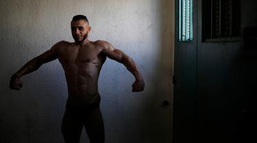 Seorang kontestan mempersiapkan diri sebelum tampil di atas panggung kompetisi binaraga lokal di Kota Gaza pada Minggu (15/9/2019). Kompetisi ini diikuti oleh sejumlah pria Palestina. (AP Photo/Hatem Moussa)