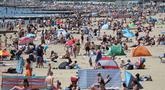 Orang-orang mencoba untuk melakukan jaga jarak ketika berjemur menikmati cuaca panas di pantai pada hari libur umum di Bournemouth, Senin (25/5/2020). Inggris mulai melonggarkan beberapa pembatasan yang diberlakukan untuk mengendalikan penyebaran virus corona Covid-19. (Andrew Matthews / PA via AP)
