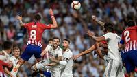 Bek Real Madrid, Nacho Fernandez, duel udara dengan gelandang Atletico Madrid, Saul Niguez, pada laga La liga di Stadion Santiago Bernabeu, Madrid, Sabtu (29/9/2018). Kedua klub bermain imbang 0-0. (AFP/Oscar Del Pozo)