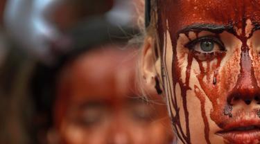 Aktivis membasahi wajahnya dengan darah palsu saat aksi menolak festival San Fermin di Pamplona, Spanyol, (5/7). Festival yang menampilkan tradisi lari bersama banteng dan matador ini merupakan aksi yang mengorbankan hewan. (REUTERS/Susana Vera)