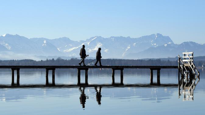Pejalan kaki berjalan melewati panorama pegunungan alpine di danau Starnberger See, Jerman (25/2). Pegunungan ini membentang dari Austria dan Slovenia di timur, melalui Italia, Swiss, Liechtenstein, Jerman sampai ke Prancis. (AFP Photo/Christof Stache)