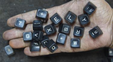 Pekerja menunjukan tombol mesin tik tua di bengkelnya di Mumbai, India (6/7). Walaupun dunia barat sudah meninggalkan, India membuktikan telah menjadi basis terakhir pertahanan penggunaan mesin ketik. (AFP Photo/Indranil Mukherjee)