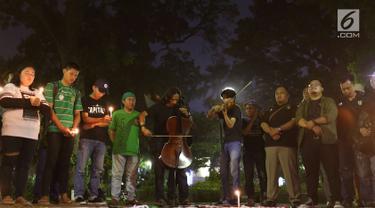 Gabungan suporter klub sepak bola bernyanyi dalam aksi solidaritas terkait tragedi teror bom di Surabaya dan Sidoarjo di Taman Suropati, Jakarta, Senin (14/5). Para suporter mengutuk teror yang terjadi di Indonesia. (Liputan6.com/Immanuel Antonius)