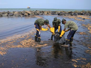 Tentara Sri Lanka membersihkan tumpahan minyak di sebuah pantai di Uswetakeiyawa, Kolombo, Senin (10/9). Pemerintah Sri Lanka mengerahkan ratusan tentara dan penjaga pantai untuk membersihkan tumpahan minyak. (AP Photo/Eranga Jayawardena)