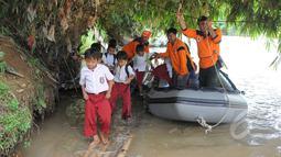 Siswa SD Negeri 1 Pajagan, Kabupaten Lebak, Banten, seusai menaiki perahu karet milik BNPB, Senin (16/3/2015). Pasca robohnya jembatan gantung di atas Sungai Ciberang, warga terpaksa menyeberang mengunakan perahu karet. (Liputan6.com/Herman Zakharia)
