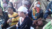 Sang istri, Ribka terisak mendapati kondisi suami dan anak semata wayangnya tak selamat akibat longsor di Manado. (Liputan6.com/Yoseph Ikanubun)